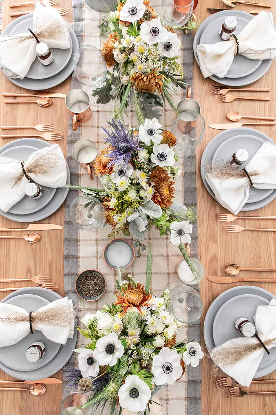 A rustic and modern tablescape with flowers, table runner, wine glasses, copper silverware.