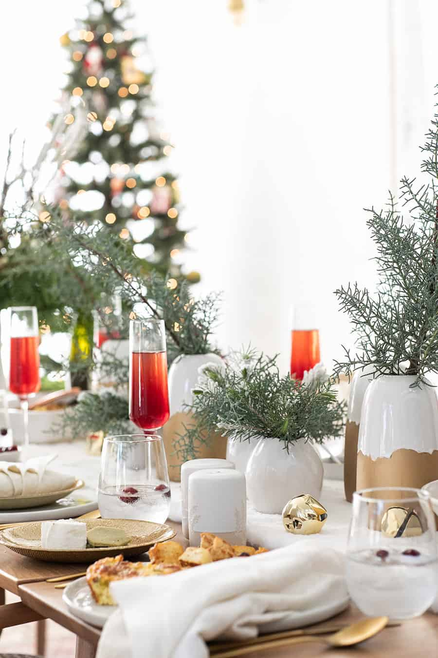 Christmas brunch table setting with white and gold and cranberry mimosas