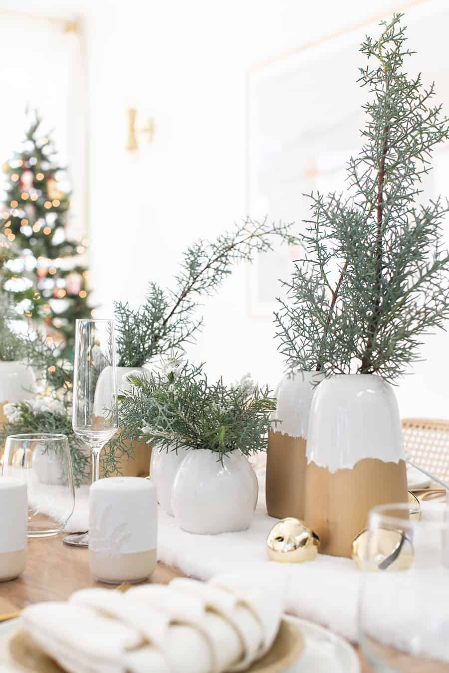 White and gold vases with holiday greens for a Christmas table setting