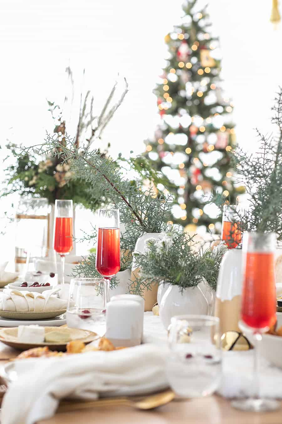 Christmas Brunch Table Setting with Cranberry Mimosas and greens in white vases.