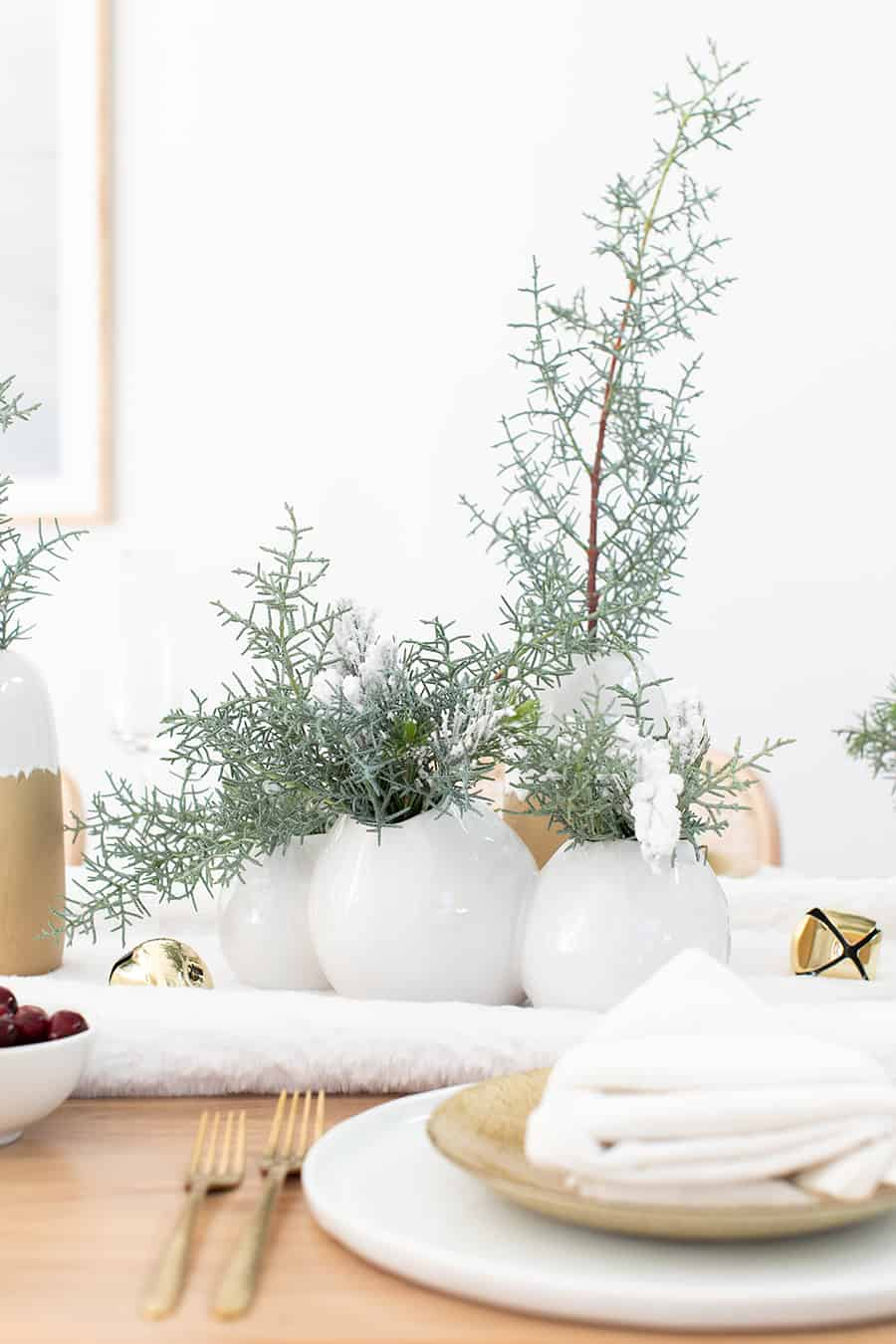 White vases filled with winter greens.
