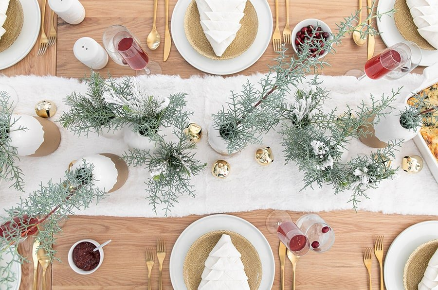 Christmas table setting with greens and a furry white table runner.