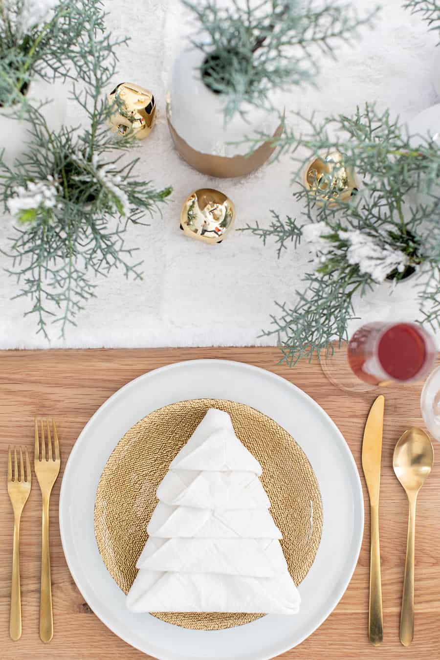White napkin folded like a Christmas tree on a gold plate with gold utensils.