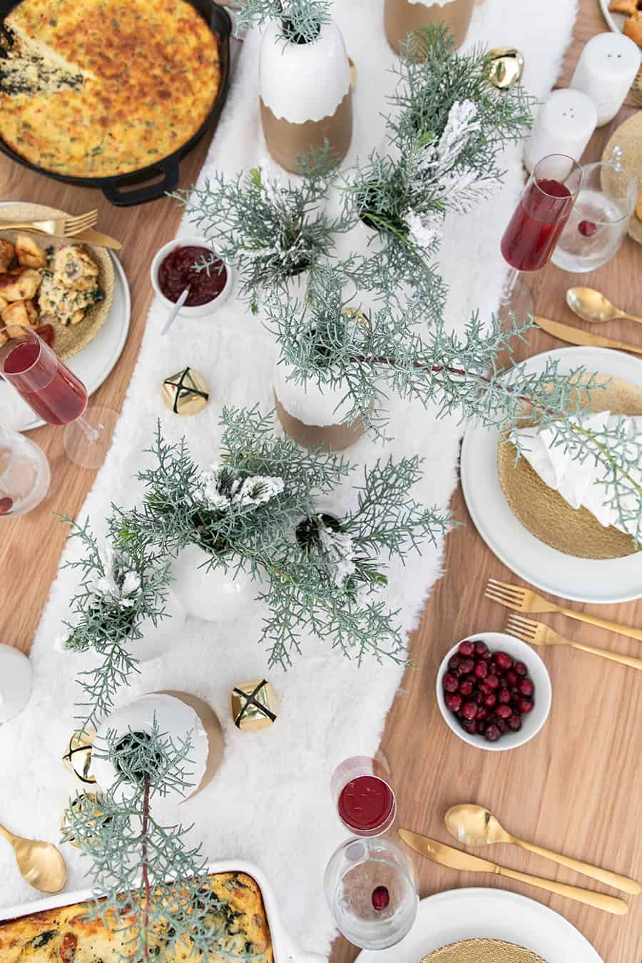Christmas brunch with greens, gold flatware and white napkins.