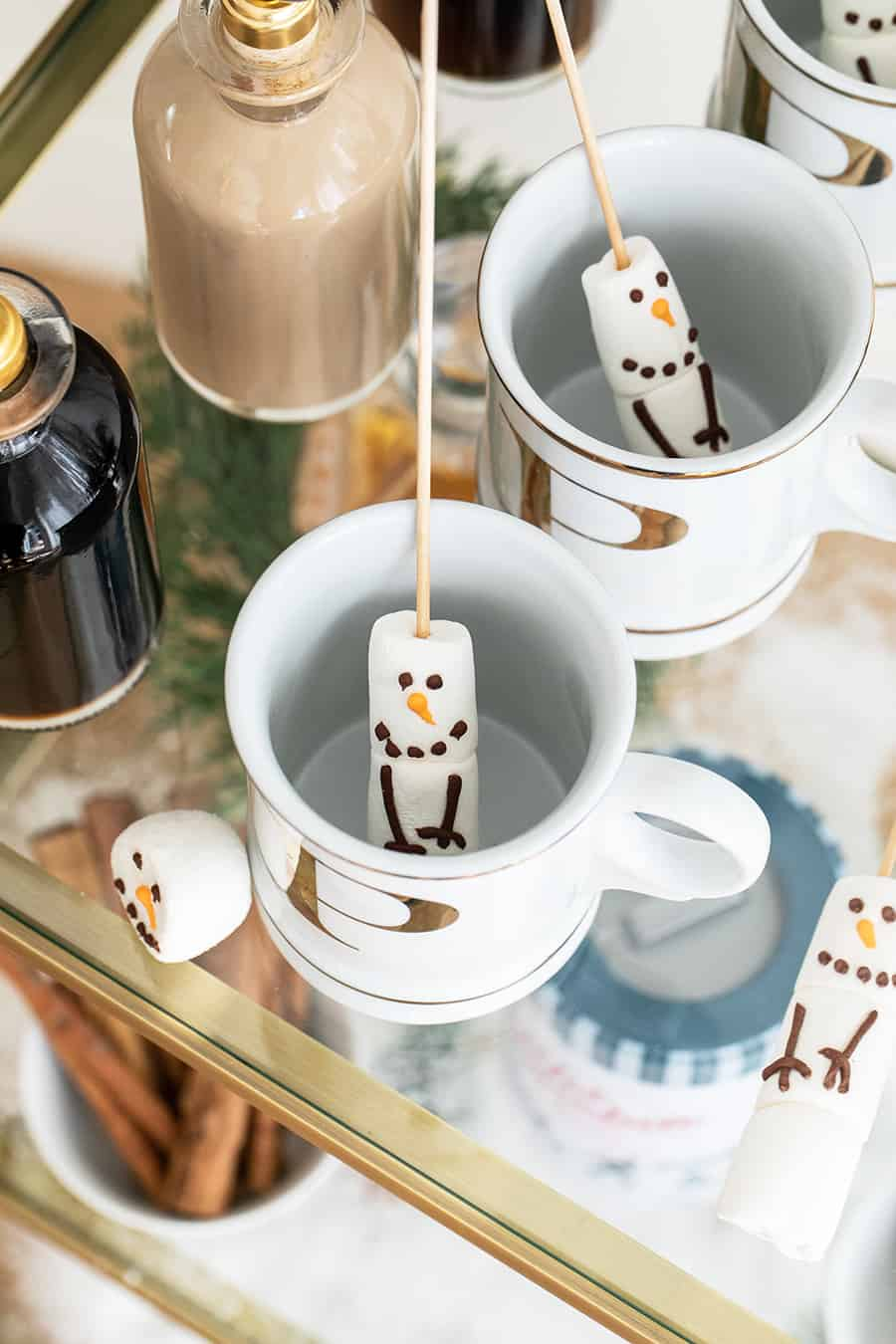 Snowman marshmallows on sticks going into a gold mug.