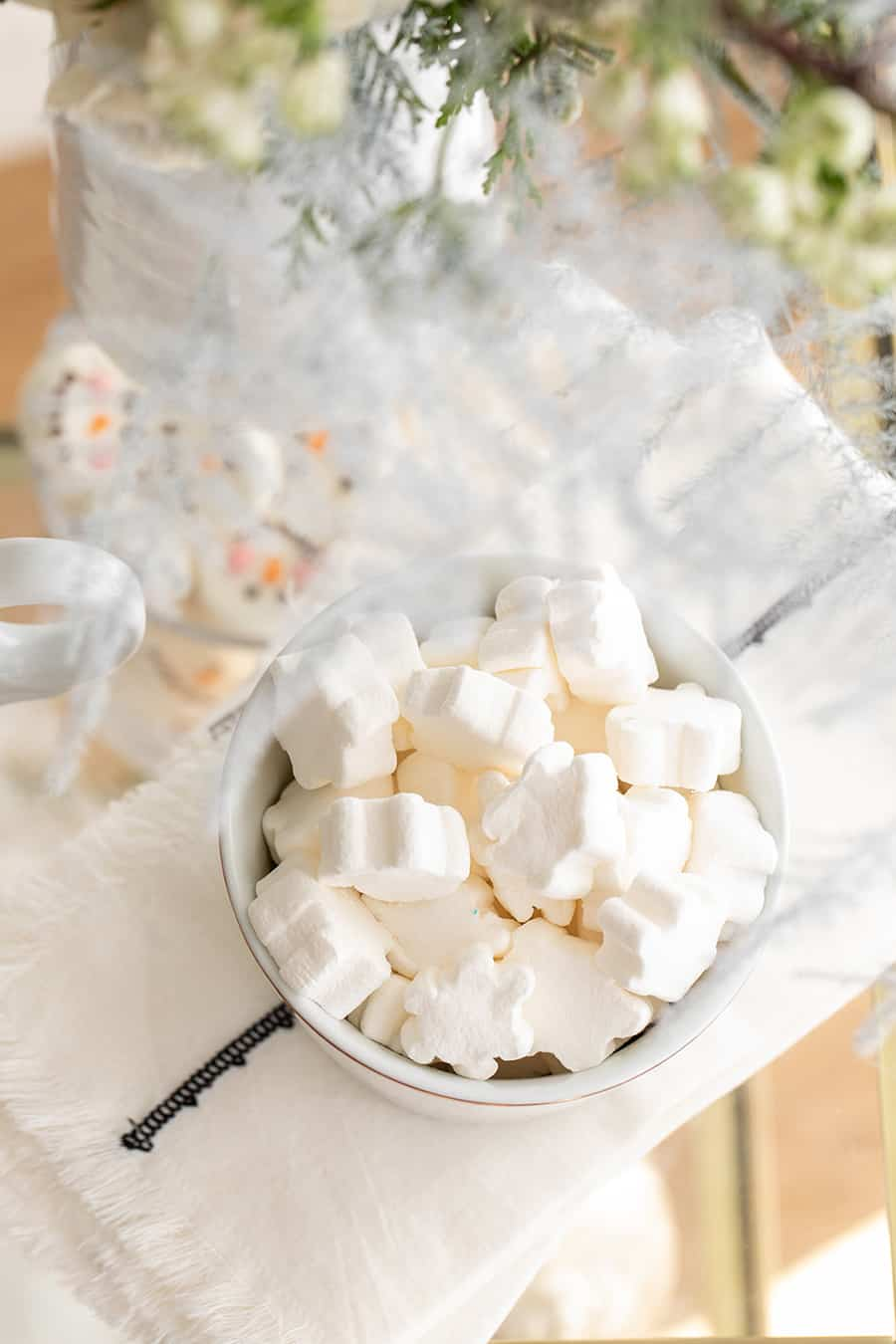 Snowflake marshmallows in a white bowl.