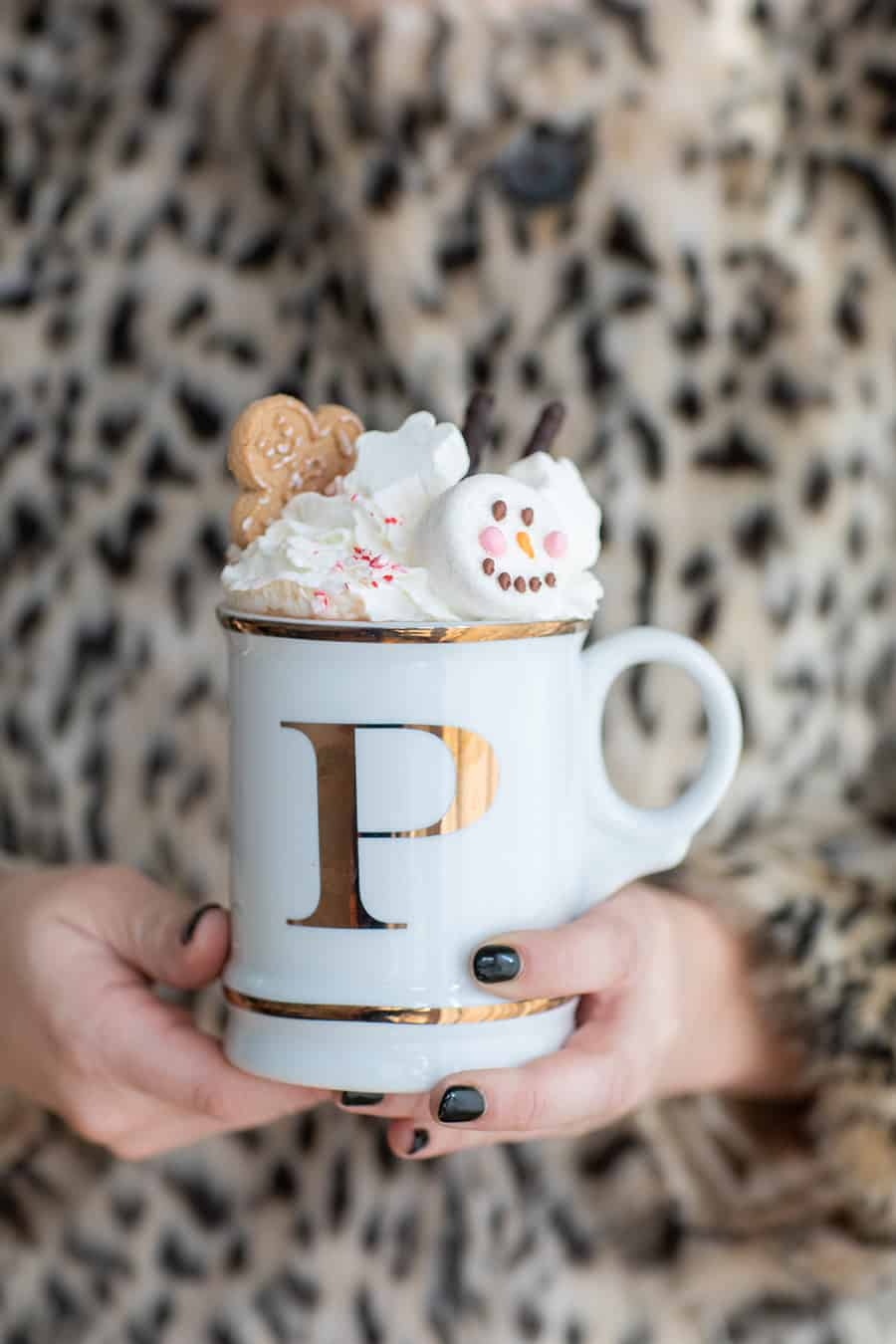 Girl holding a mug of hot chocolate topped with whipped cream, cookies and marshmallow.