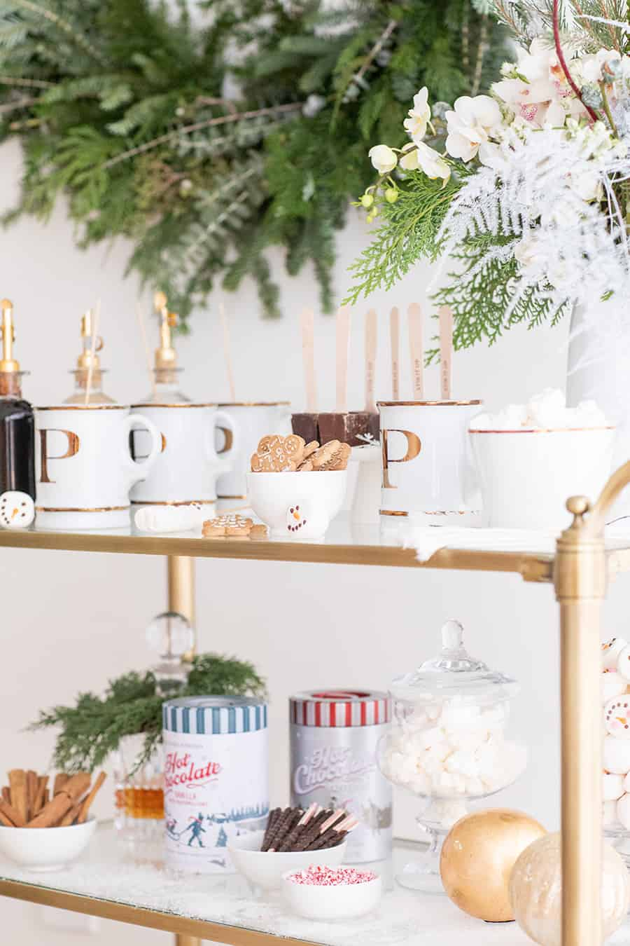 Hot cocoa, mugs, marshmallows and flowers on a brass bar cart.