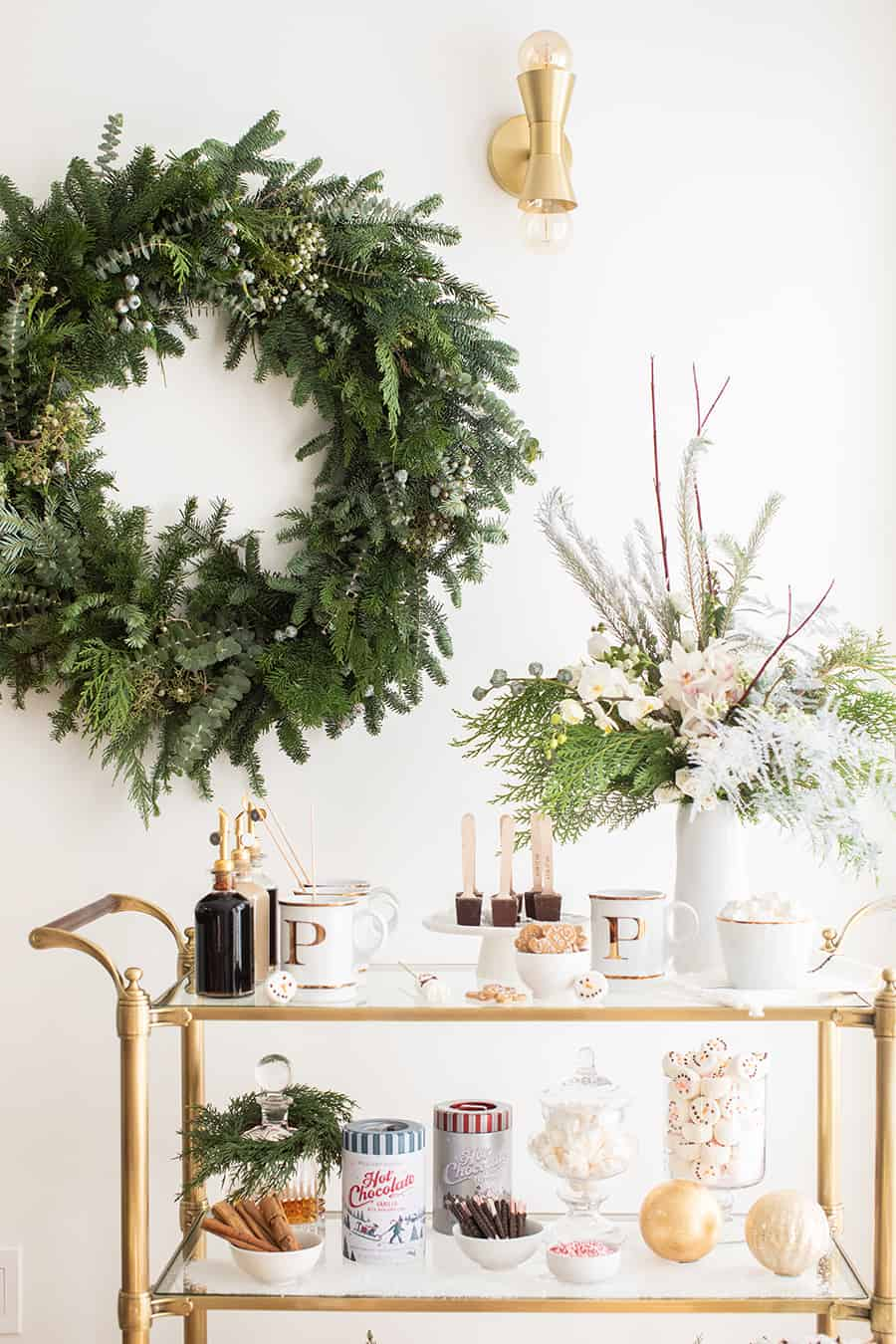 Hot chocolate bar with a Christmas wreath, mugs, syrups, flowers and holiday hot chocolate all placed on a brass bar cart.