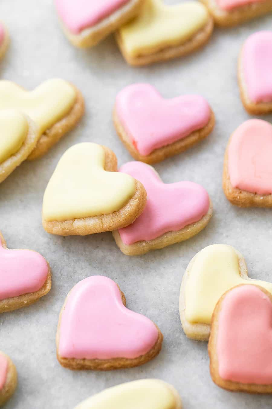 mini heart shaped sugar cookies in yellow and pink on a marble table