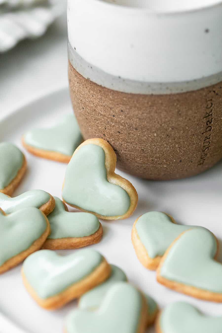 mini heart shaped sugar cookies on a plate with coffee