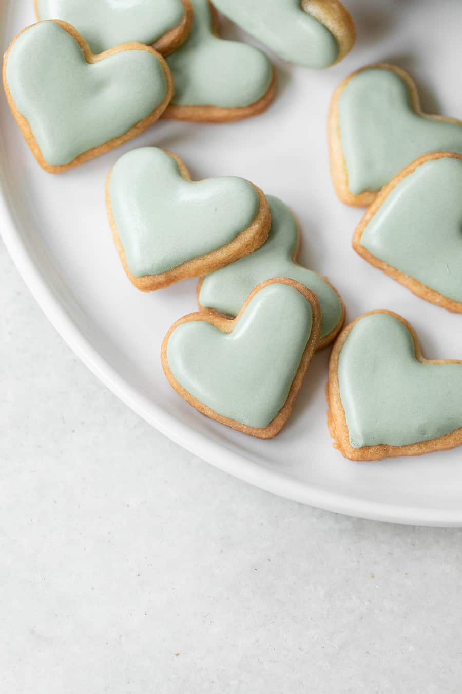 mini blue heart shaped cut out sugar cookies with blue royal icing