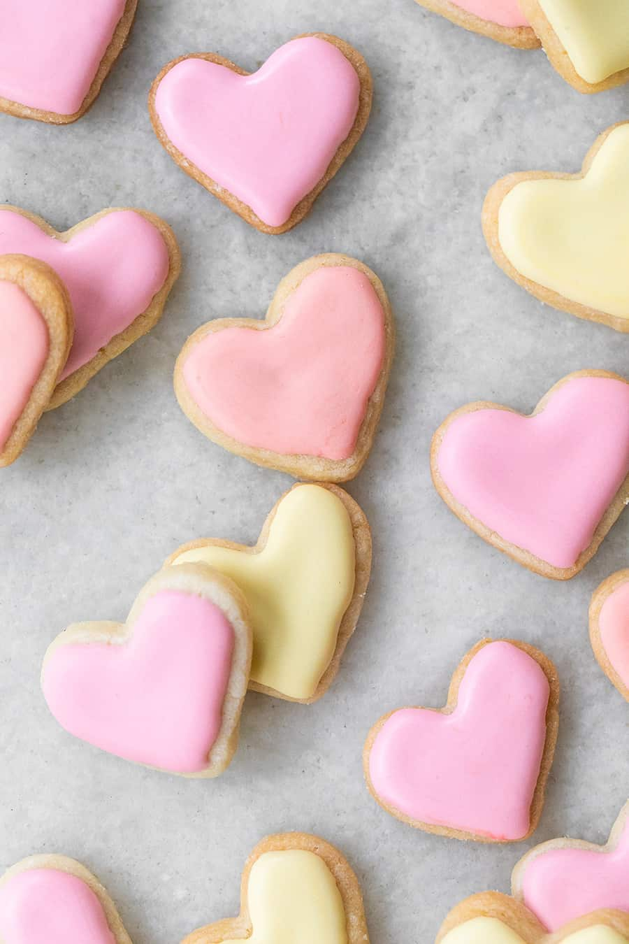 mini heart shaped sugar cookies frosting in pink and yellow royal icing on a marble table.