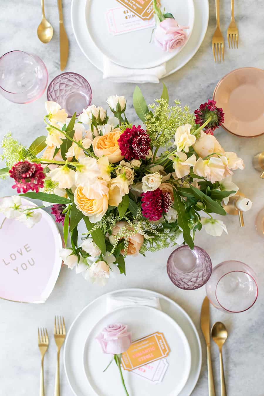 Romantic flowers in the center of a table with pink, white and gold dishes.