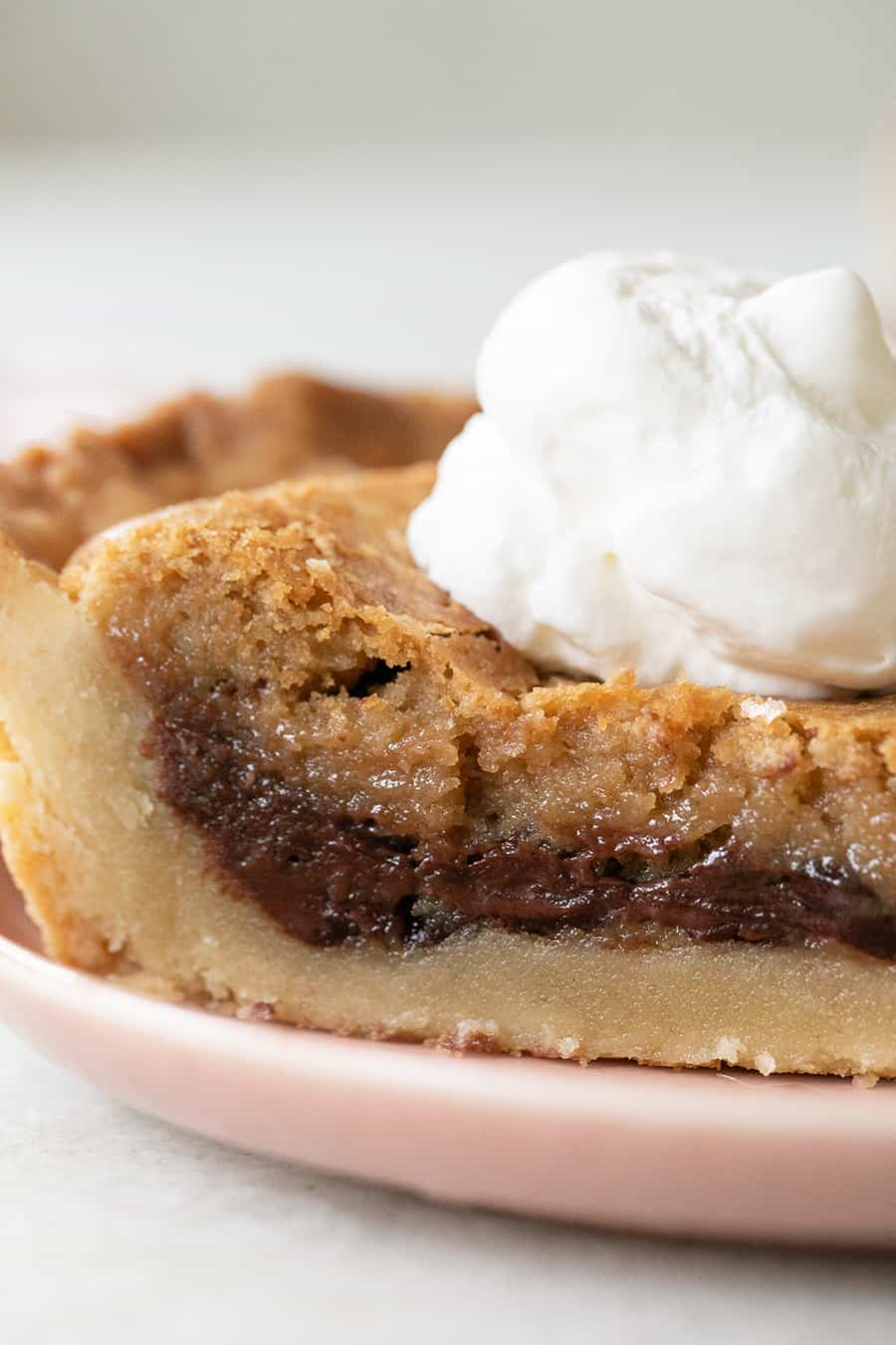 Close up photo of a chocolate chip cookie pie with shortbread cookie pie crust and whipped cream.