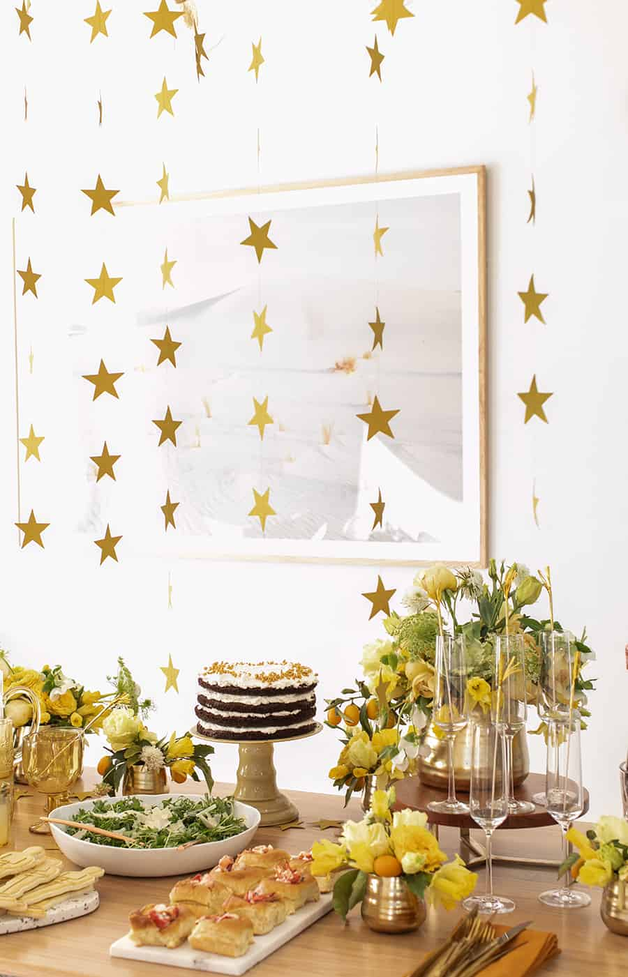 Gold stars hanging from ceiling for Oscar party decorations.