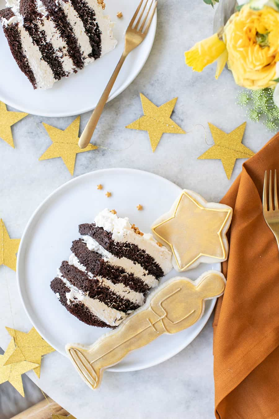 Oscar party tuxedo cake on white plate with cookies.