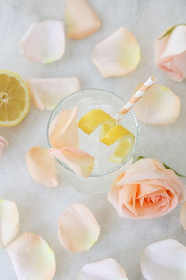 Cocktail with lemon and rose petals.