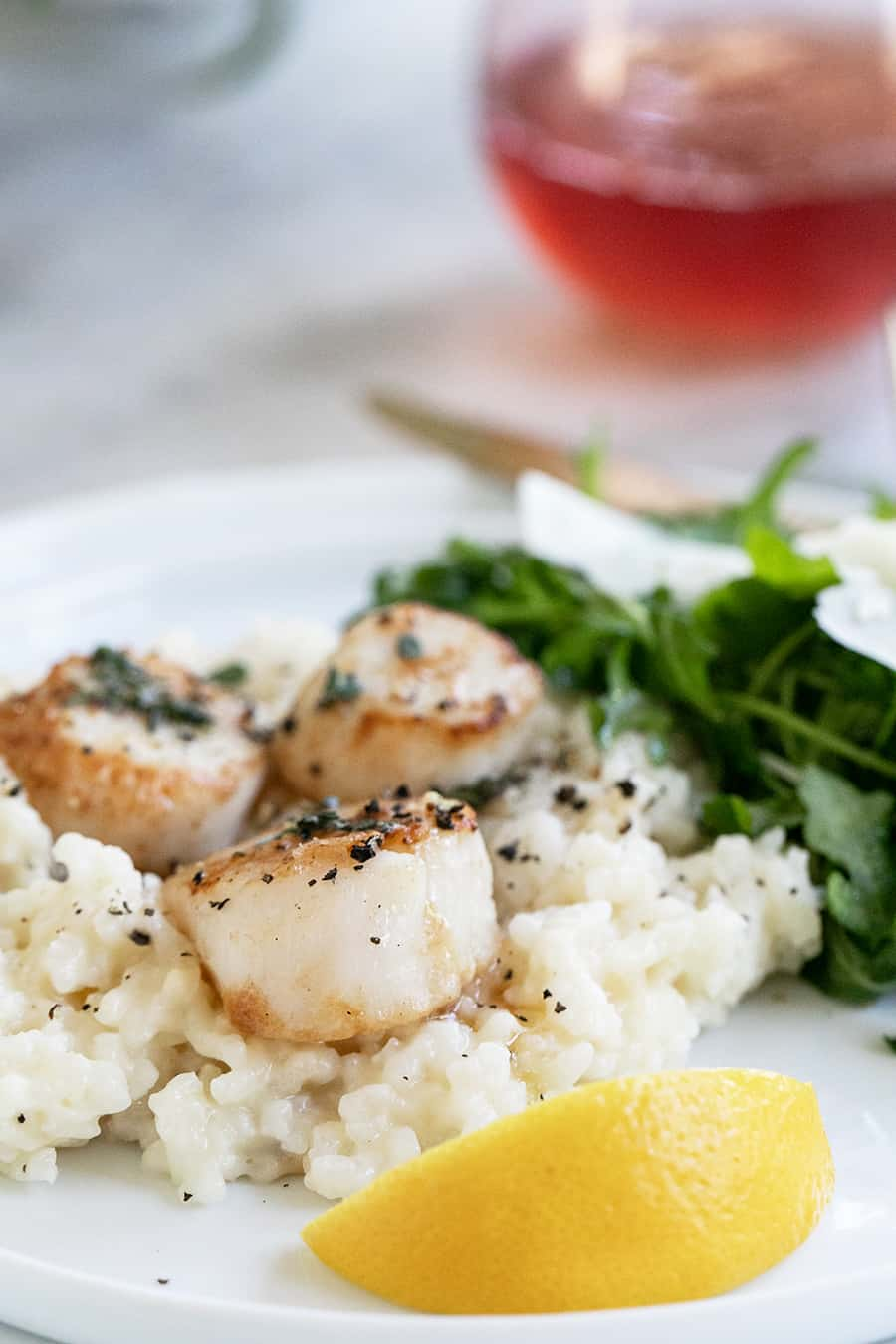 Scallops and risotto with lemon on a white plate.