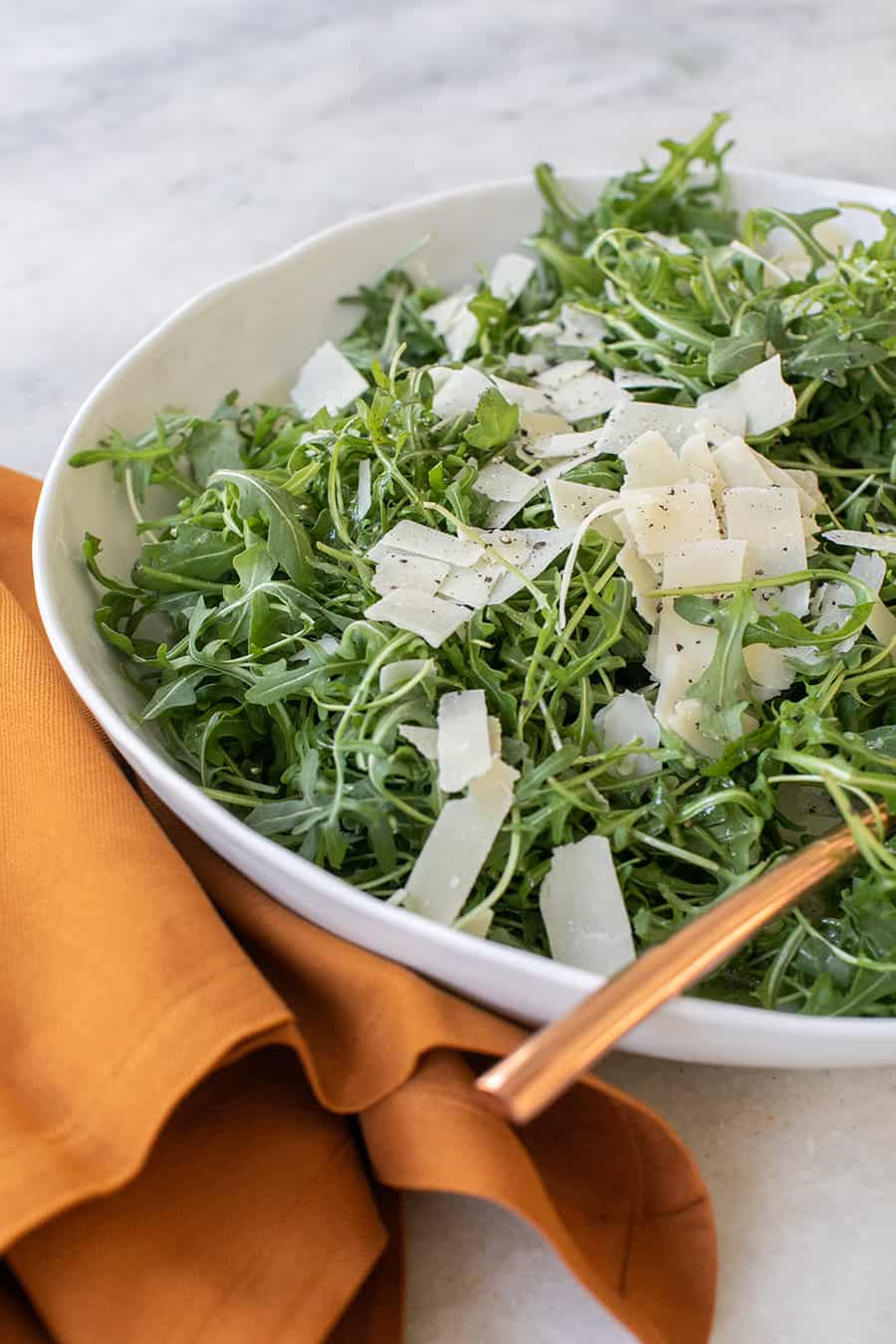 side shot of simple salad with parmesan on top