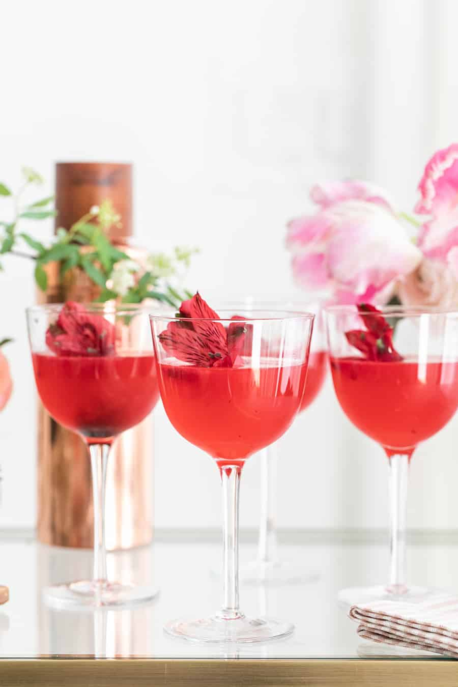 Beautiful pink cocktails garnished with flowers.