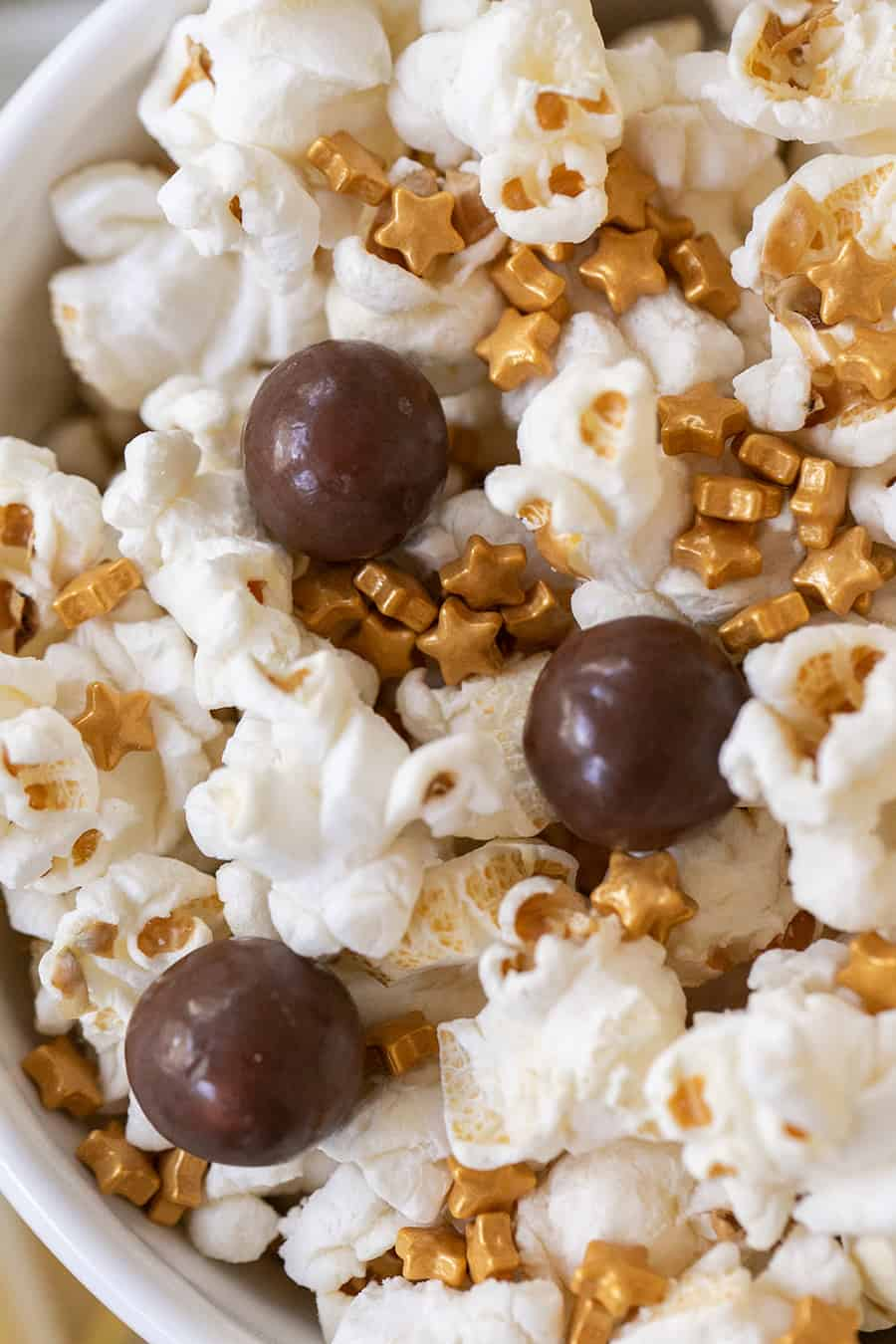 Popcorn with chocolate malt balls and gold sprinkles.