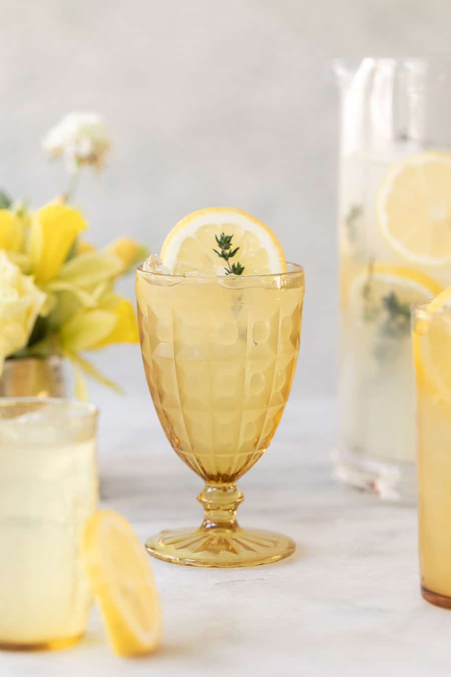 Spiked lemonade in yellow glasses with sprig of thyme