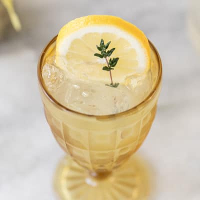 lemonade in yellow glass with thyme sprig
