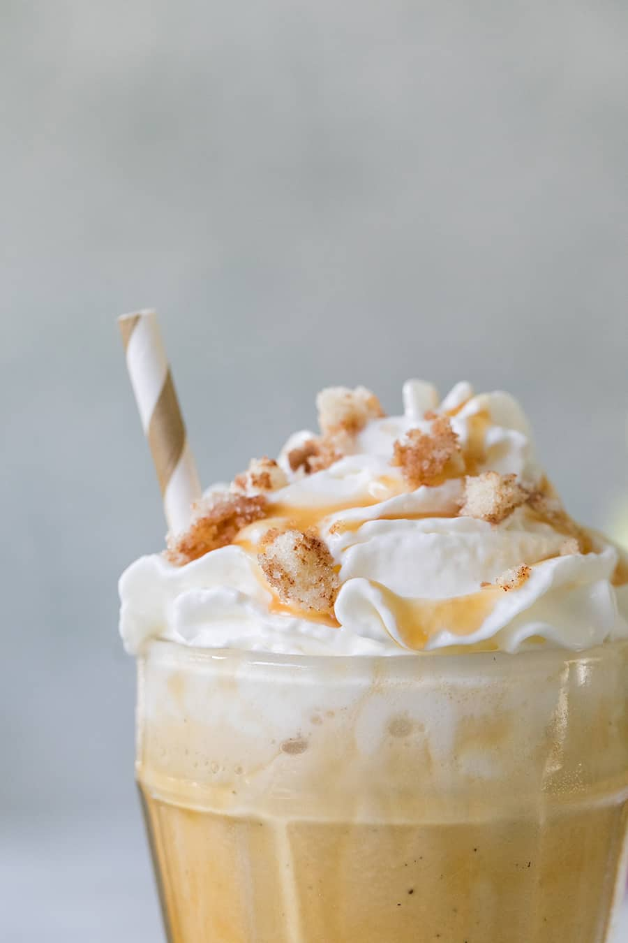 close up picture of a caramel coffee milkshake, with whipped cream and caramel on the top