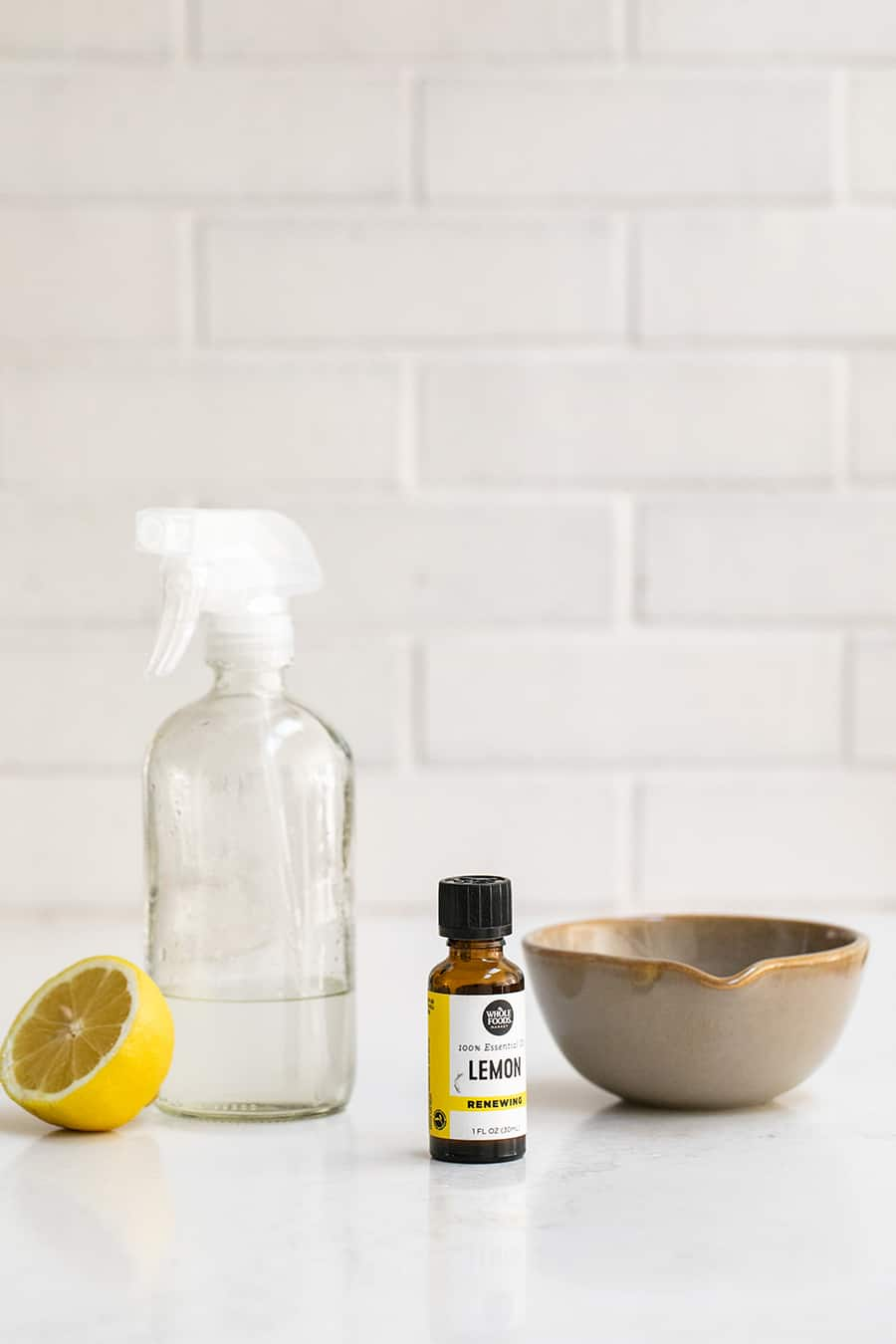 Lemon Oil, Lemon, Vinegar and a Clear Spray Bottle to make Natural Window Cleaner