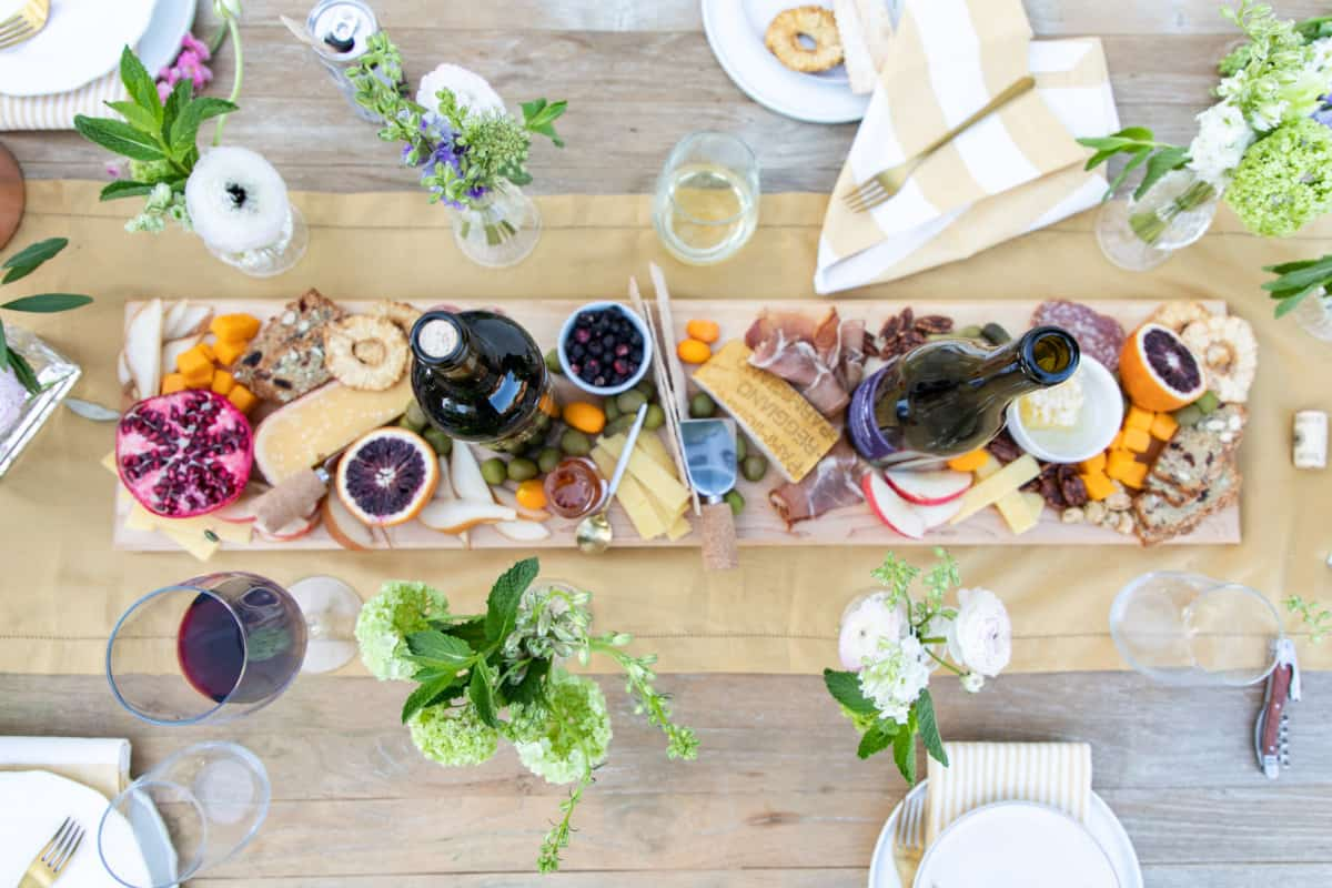 Overhead of cheese board and wine bottles.