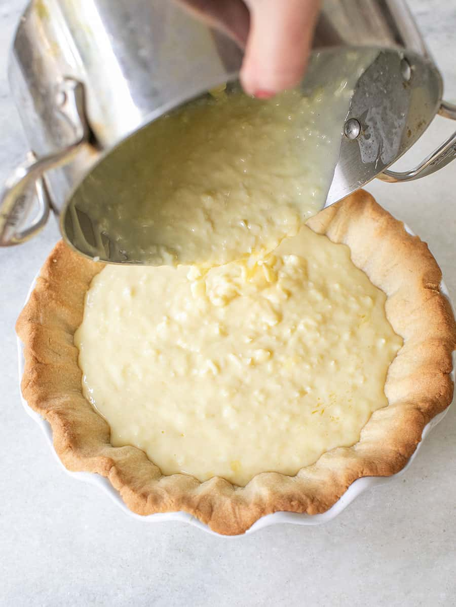 Coconut cream pie being poured into a shortbread cookie crust.