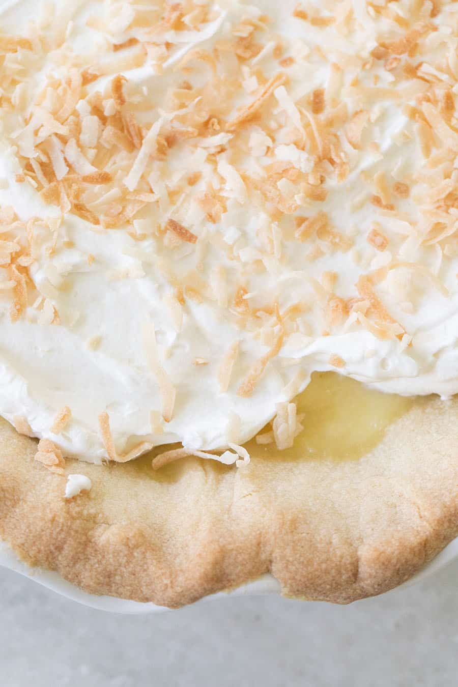 Close up photo of whipped cream, toasted coconut on a coconut cream pie.