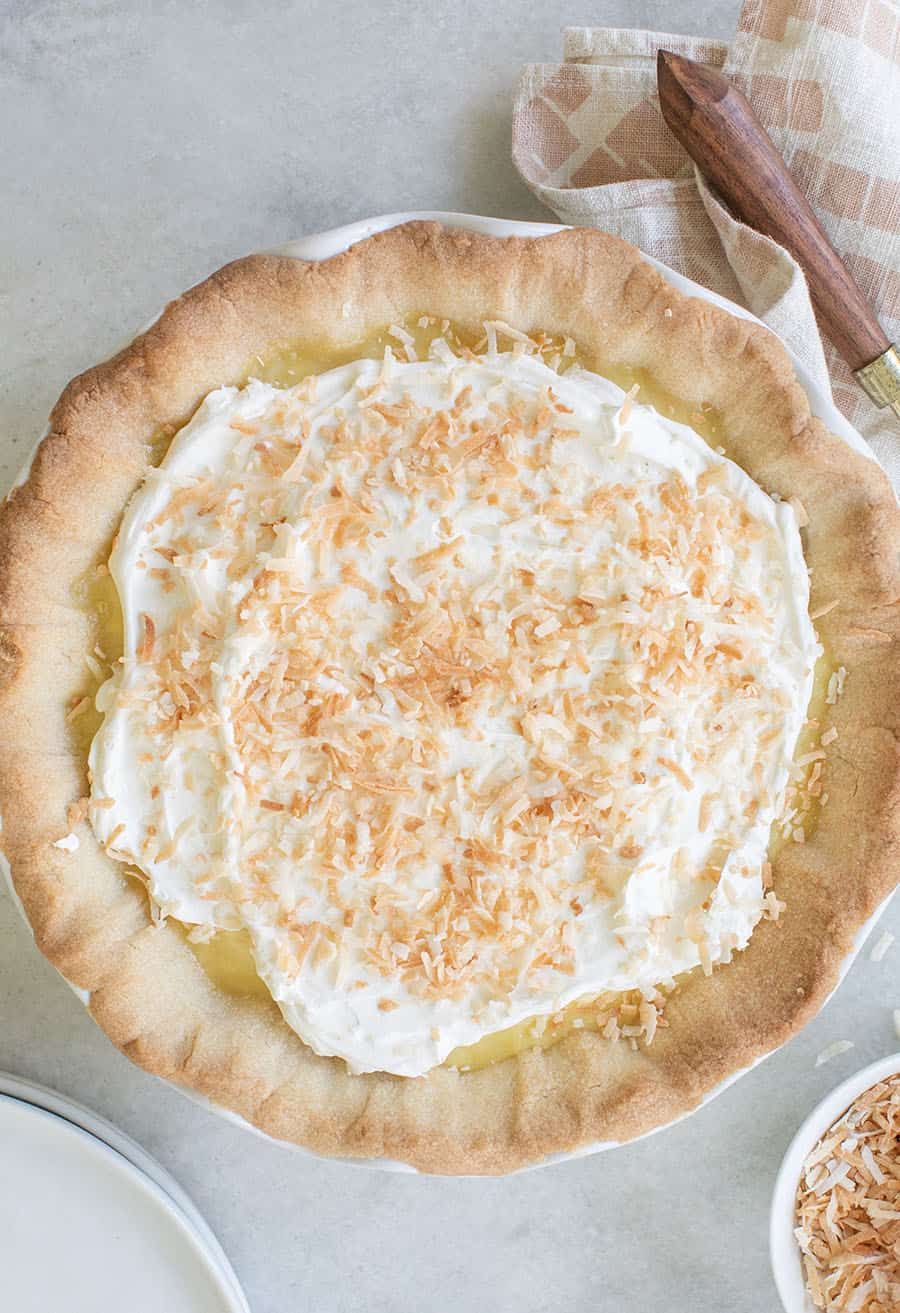 Coconut cream pie recipe with homemade whipped cream and coconut shreds.