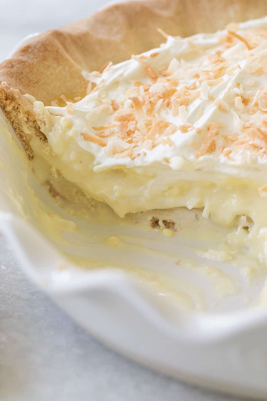 A slice of coconut cream pie removed from a pie dish