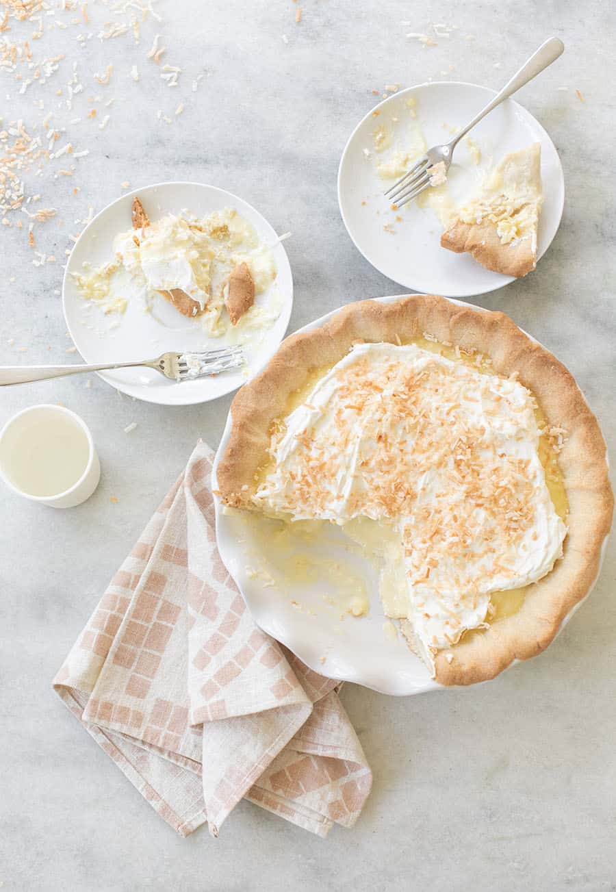 Coconut cream pie on two plates on a marble table.