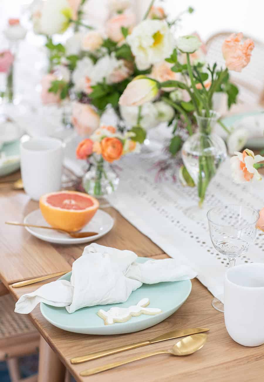 Easter brunch table setting with napkin and gold silverware.