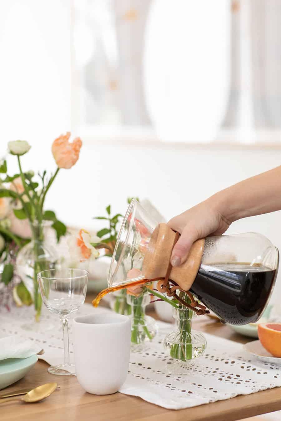 Eden Passante pouring coffee into a coffee mug.