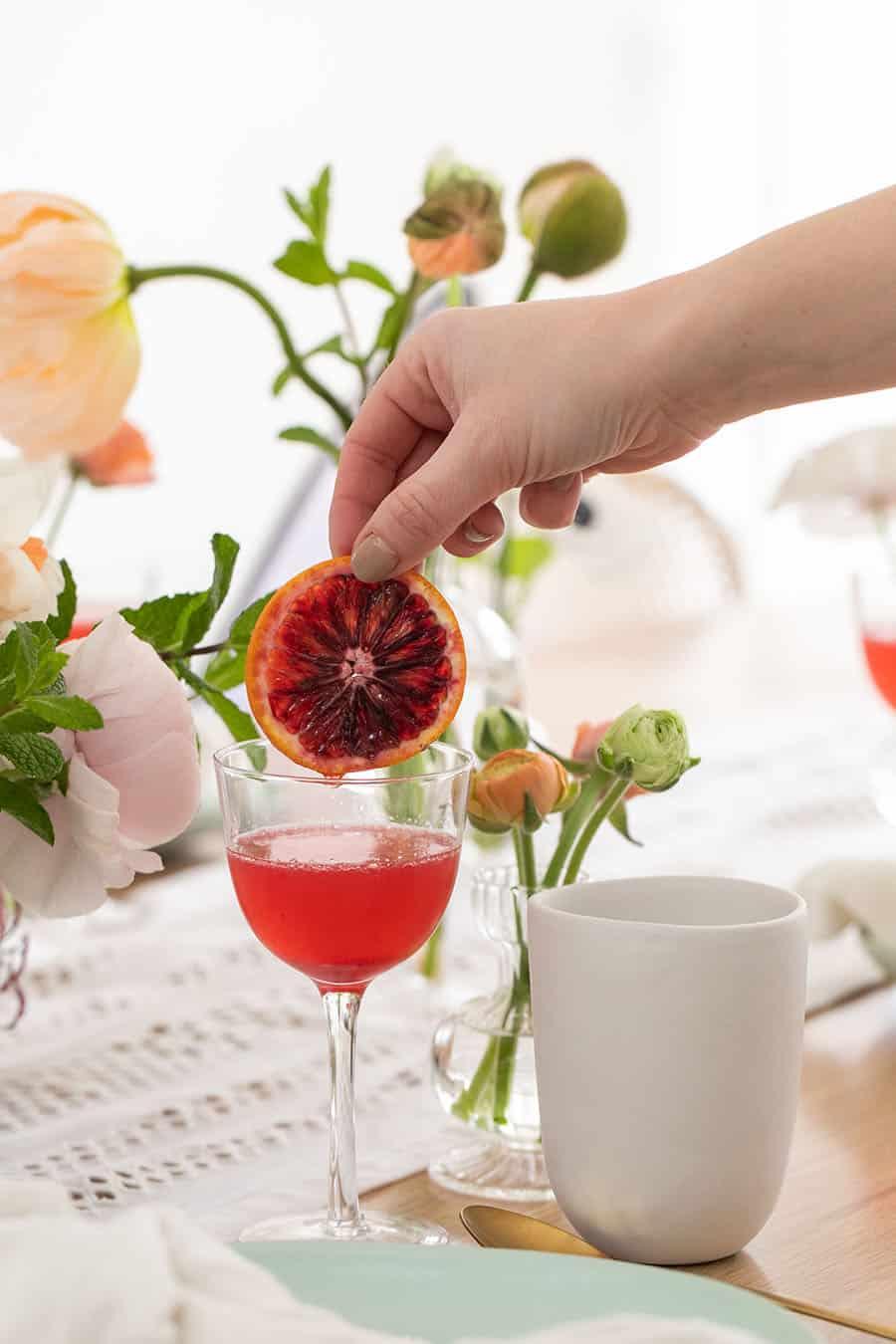 Eden Passante adding a blood orange slice into a blood orange mimosa.