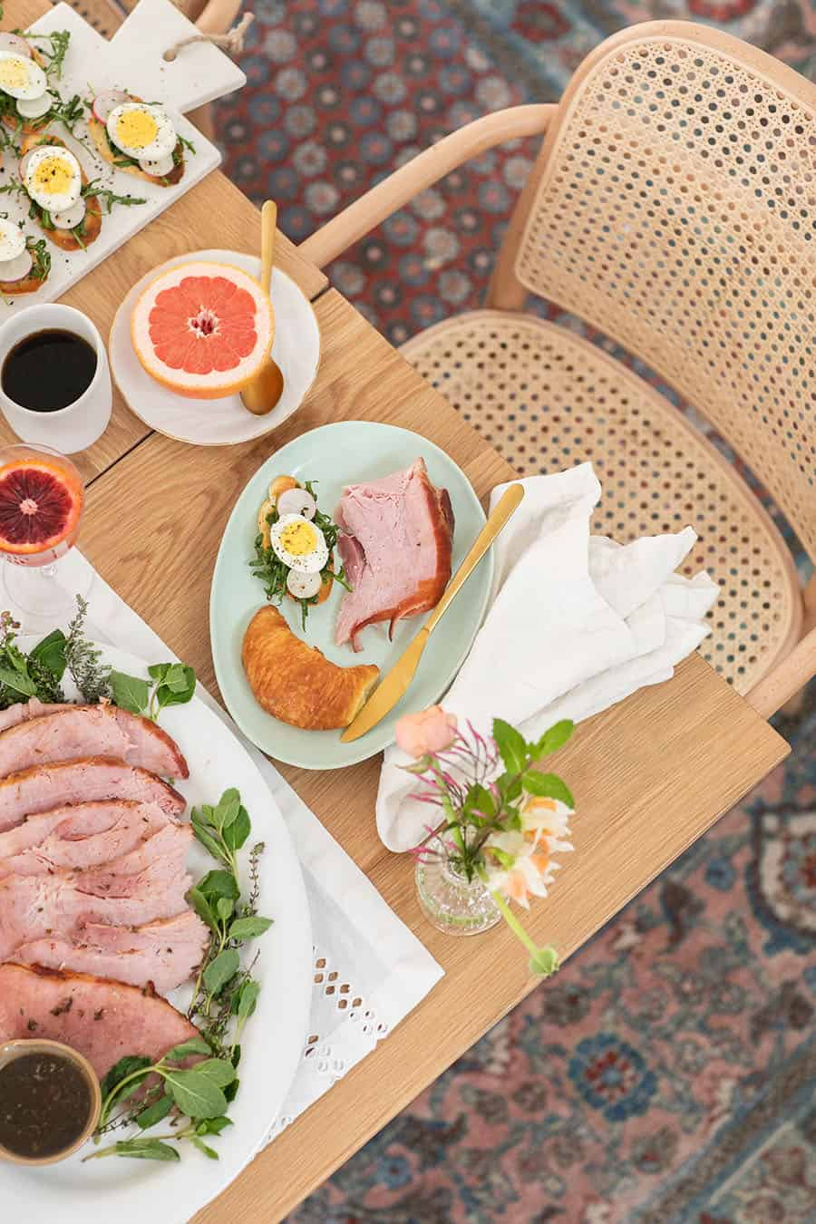 Overhead of an Easter brunch table setting with ham and food.