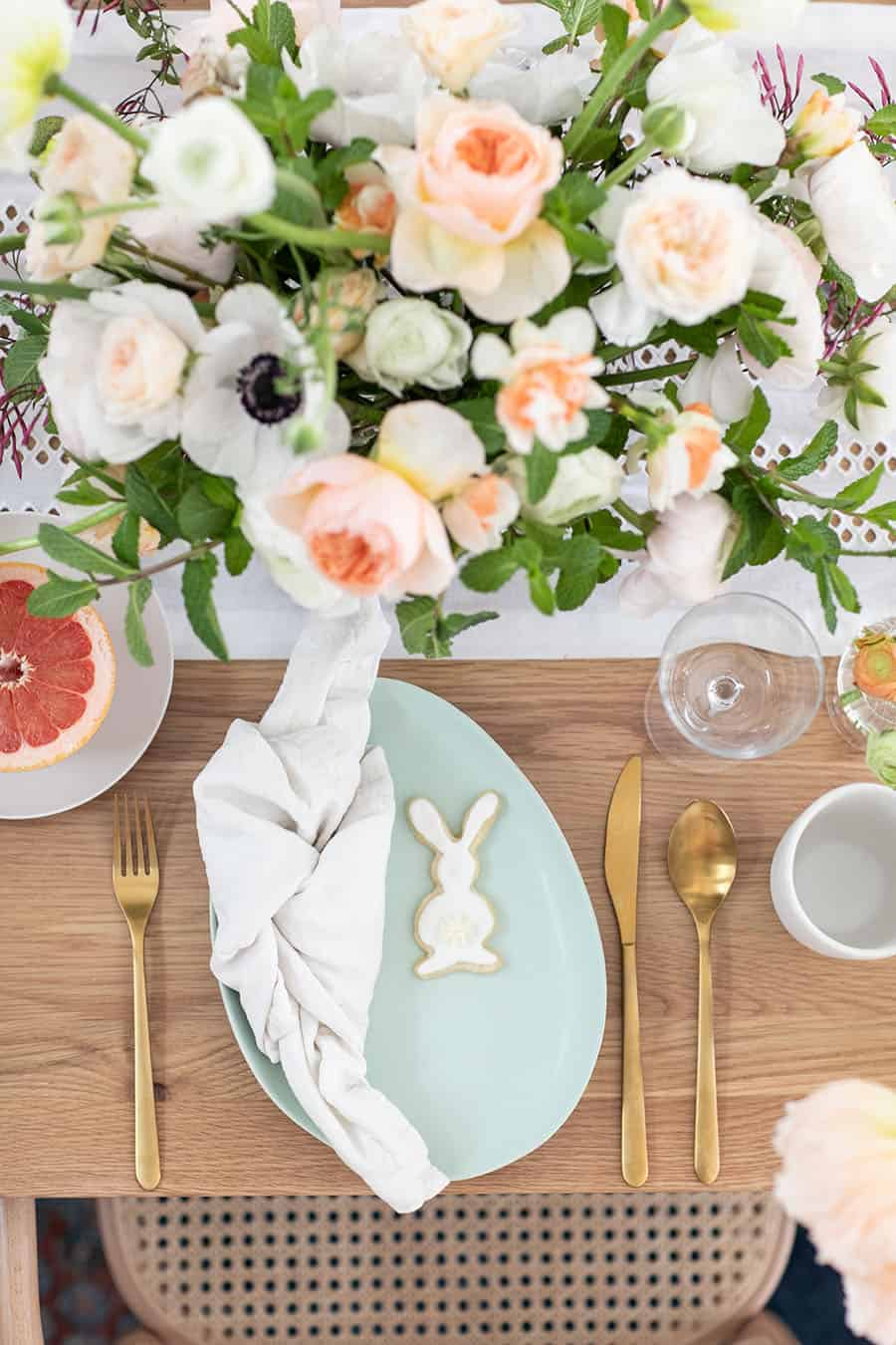 Beautiful table setting for an Easter brunch with blue dishes, glasses and flowers.