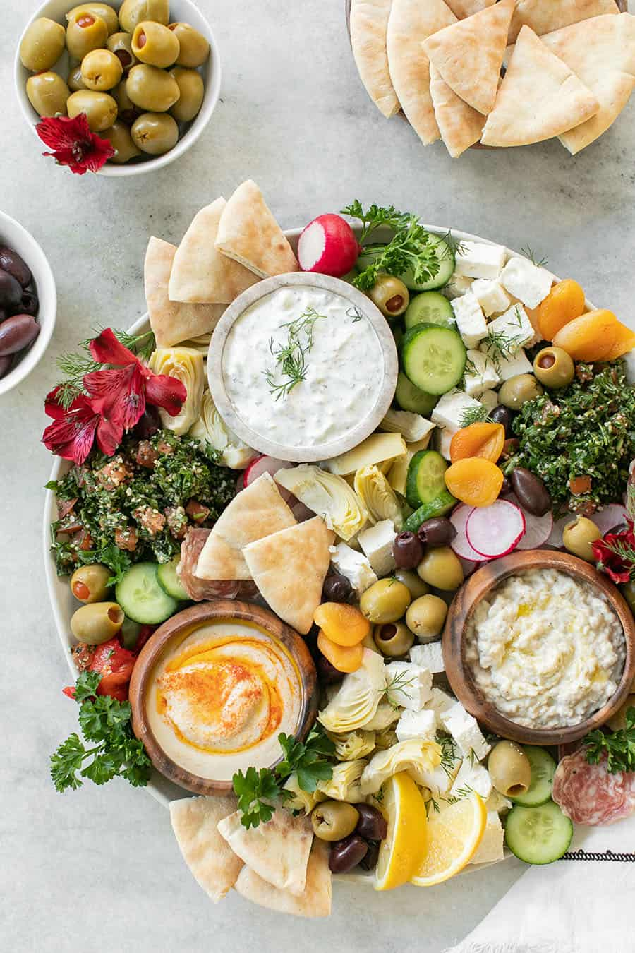 Easy Greek Mezze Platter on a marble table with dips, bread, olives and feta.