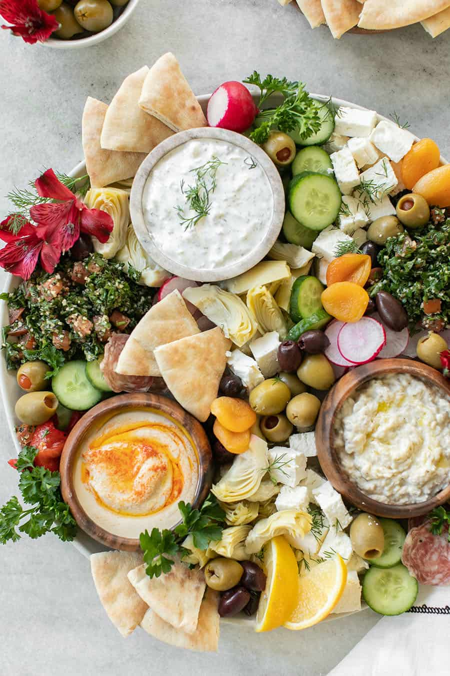 Easy Greek Mezze Platter with yogurt and pretty toppings like olives, radish, bread.