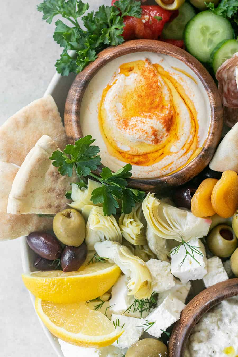 Easy Greek Food Mezze Platter with hummus, lemons, olives, and herbs.