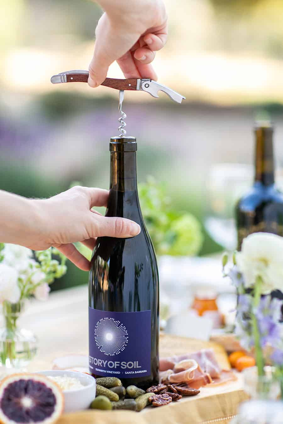 Hand opening a wine bottle with a corkscrew opener.