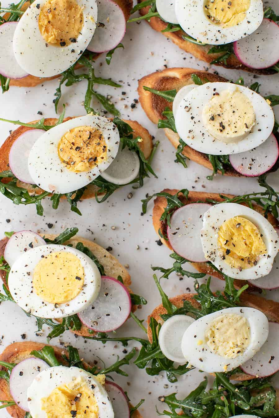 Crostini recipe with hard boiled eggs, radish, arugula and salt and pepper.