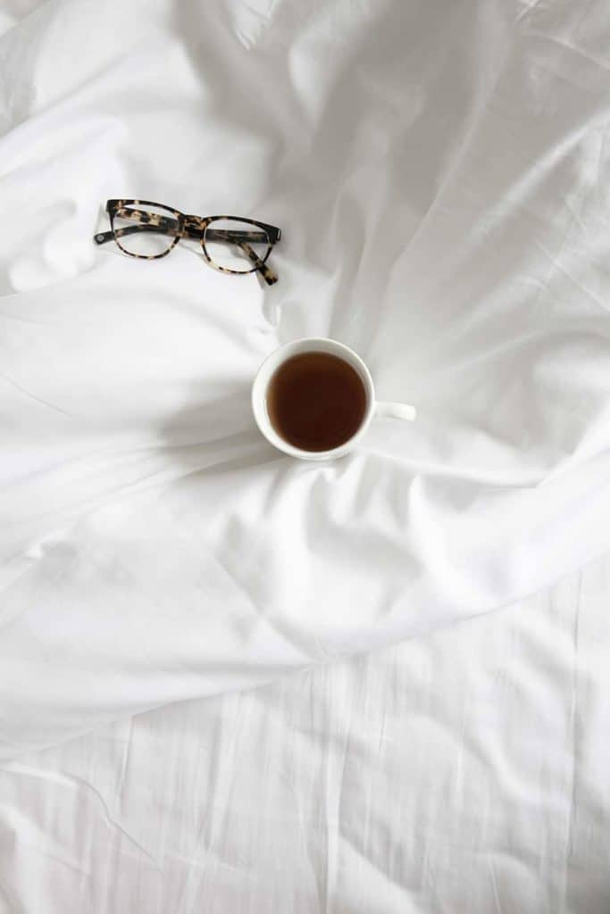 Photo of coffee on bed sheets.