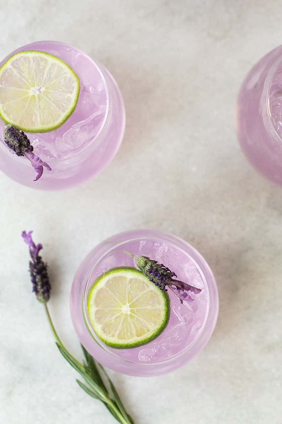 Purple ginned tonic punch with a lime slice on a marble table.