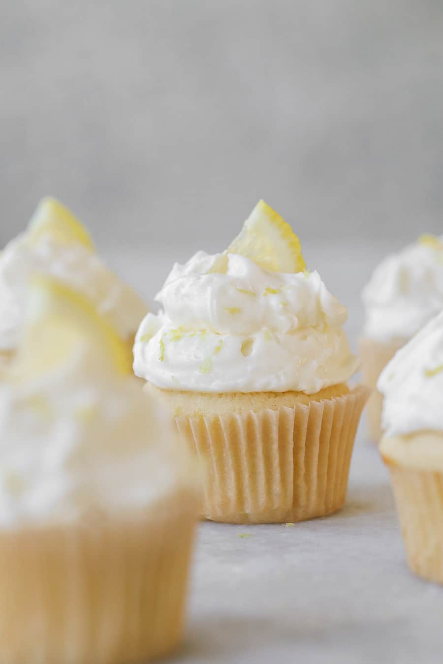 Lemon Cupcakes with Buttercream Meringue Frosting with a lemon wedge and lemon zest
