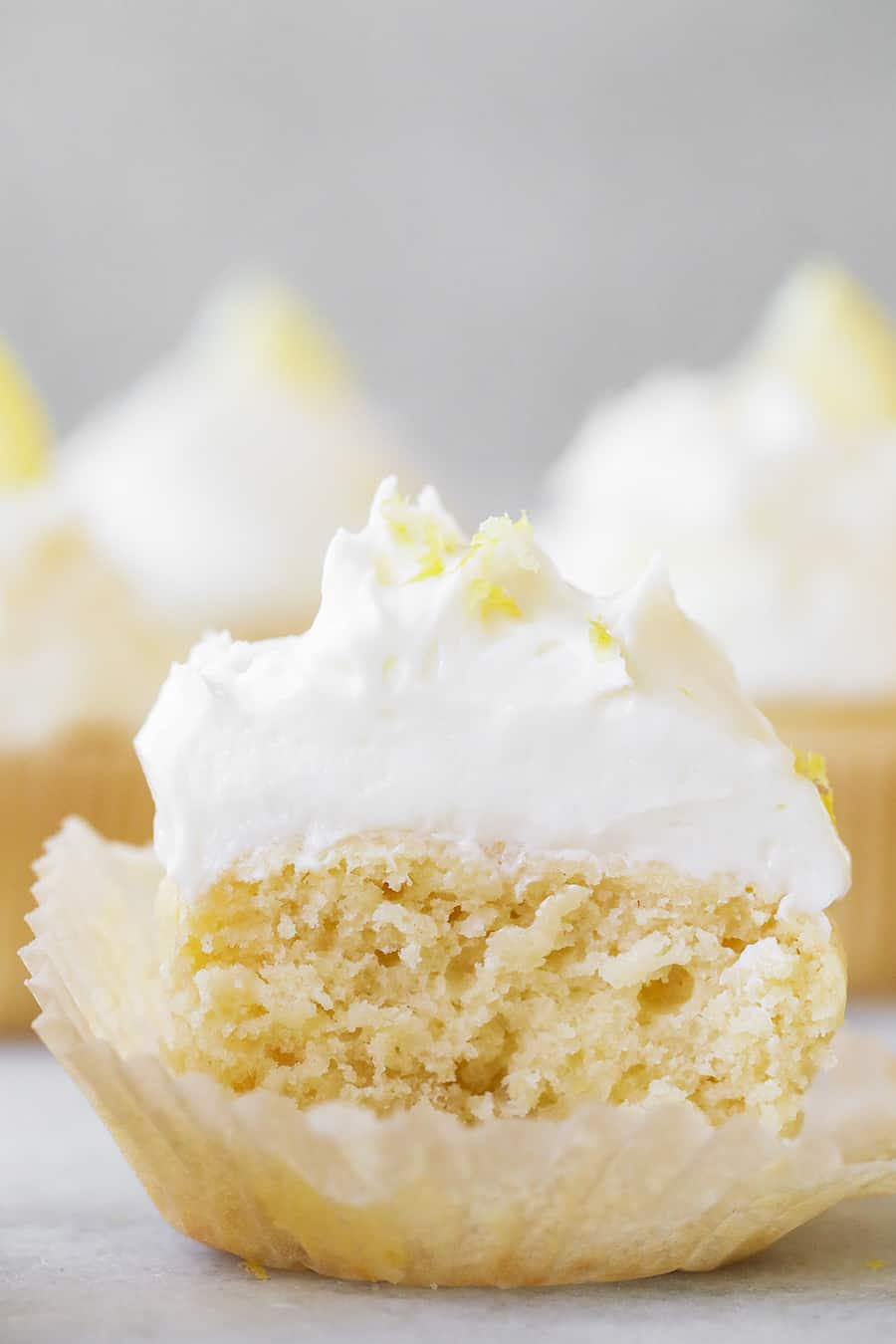 Lemon Cupcakes with Buttercream Meringue Frosting cut in half.
